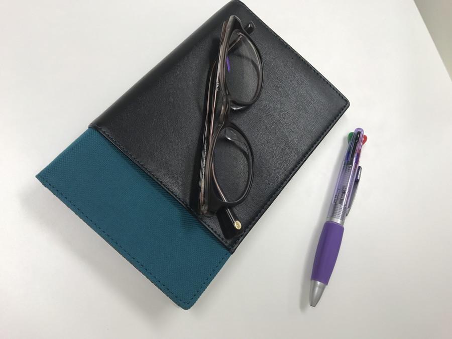 机の上にあるノート、めがね、ペン